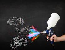 El hombre con la pintura de espray del aerógrafo con el coche, el barco y la motocicleta dibujan Fotografía de archivo