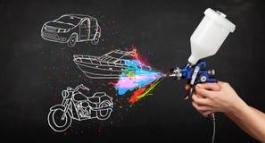 El hombre con la pintura de espray del aerógrafo con el coche, el barco y la motocicleta dibujan Imagen de archivo libre de regalías