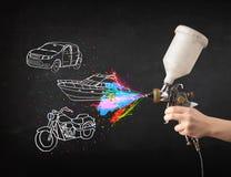 El hombre con la pintura de espray del aerógrafo con el coche, el barco y la motocicleta dibujan Imagenes de archivo