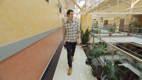 El hombre con la tableta va al tercer piso del atrio, rodeado por la vegetación almacen de metraje de vídeo