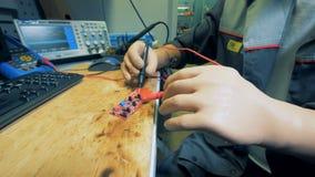 El hombre con las manos prostéticas está soldando un microscheme