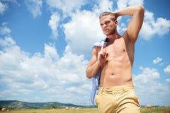 El hombre con las tetas al aire al aire libre con la mano en pelo mira lejos Fotos de archivo