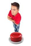 El hombre con los brazos cruzó encima de un botón rojo Imágenes de archivo libres de regalías