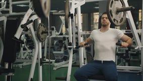 El hombre con los deportes figura hacer ejercicio en el simulador en el gimnasio metrajes