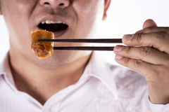 El hombre con los palillos come el springroll del huevo Fotografía de archivo