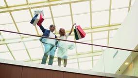 El hombre con los regalos de la compra de la mujer para la Navidad Paquetes multicolores grandes en manos en los compradores del  metrajes