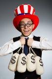 El hombre con los sacos del dinero del dólar Imágenes de archivo libres de regalías