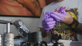 El hombre con los tatuajes pone el primer de los guantes almacen de metraje de vídeo