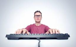 El hombre con los vidrios está mecanografiando en un teclado mientras que se sienta delante de un ordenador fotos de archivo libres de regalías