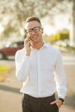 El hombre con los vidrios habla en el teléfono móvil en manos Fotografía de archivo libre de regalías