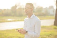 El hombre con los vidrios habla en el teléfono móvil en manos Imágenes de archivo libres de regalías