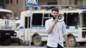 El hombre con el megáfono grita en la calle en la ciudad contra el contexto de un coche policía almacen de video