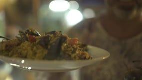 El hombre con el plato tradicional de la paella a disposición se preparó en restaurante español Hombre que sostiene la paella esp almacen de metraje de vídeo