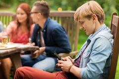 El hombre con smartphone y los amigos en el verano van de fiesta Fotografía de archivo libre de regalías