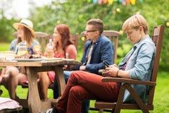 El hombre con smartphone y los amigos en el verano van de fiesta Imagenes de archivo