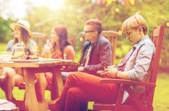 El hombre con smartphone y los amigos en el verano van de fiesta Imagen de archivo