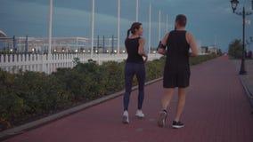 El hombre con su novia está activando junto en el área del deporte, charlando feliz almacen de video