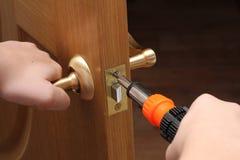 El hombre con un destornillador en su mano repara la puerta interna Bloqueo de puerta Imagenes de archivo