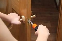 El hombre con un destornillador en su mano repara la puerta interna Bloqueo de puerta Imagen de archivo