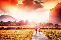 El hombre con un hijo joven va abajo de la trayectoria en la puesta del sol en un fondo Foto de archivo