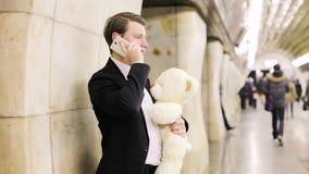 El hombre con un oso del juguete llama su querido almacen de metraje de vídeo