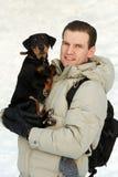 El hombre con un perrito en las manos Fotografía de archivo