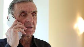 El hombre con un smartphone blanco habla almacen de metraje de vídeo