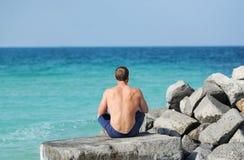 El hombre con un torso desnudo que se sienta en una piedra con ella detrás que mira el mar fotografía de archivo