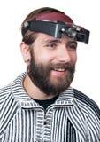 El hombre con una barba en magnificar señala Imagen de archivo libre de regalías