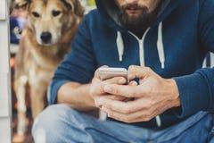 El hombre con una capilla y un perro utiliza el smartphone foto de archivo