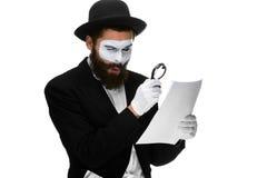 El hombre con una cara imita la lectura con magnificar Fotos de archivo libres de regalías