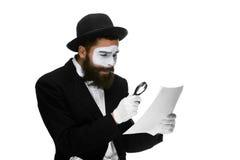 El hombre con una cara imita la lectura con magnificar Imagen de archivo libre de regalías