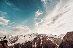 el hombre con una mochila en camuflaje sube al top de la montaña Fotos de archivo