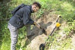 El hombre con una pala en sus manos cava un agujero en la tierra en busca de artículos militares El detector de metales miente al imágenes de archivo libres de regalías
