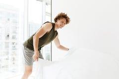 El hombre concentrado hace la cama en casa dentro imagen de archivo