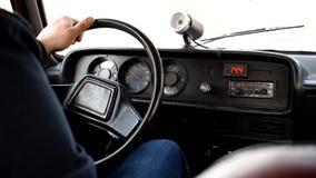El hombre conduce un coche viejo