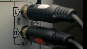 El hombre conecta el cable AUX. Conector de audio metrajes