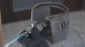 El hombre conecta el cilindro de gas metrajes