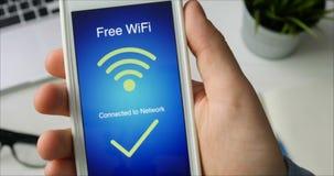 El hombre conecta con la red libre del wifi usando su smartphone que se sienta en el escritorio metrajes