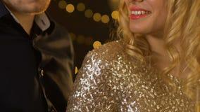 El hombre confiado que da el vidrio de champán a la señora bonita en vestido de oro, se relaja almacen de metraje de vídeo