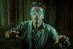 El hombre confuso y asustado joven vendado los ojos de con la corbata que jugaba desafío viral peligroso de la tendencia de Inter imagen de archivo
