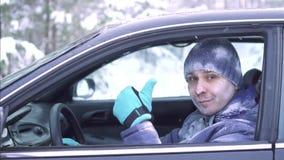 El hombre congelado alegre se sienta en el coche y las demostraciones manosean con los dedos para arriba metrajes