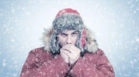 El hombre congelado en invierno rojo viste las manos que se calientan, frío, nieve, helada, ventisca foto de archivo