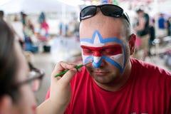 El hombre consigue el símbolo de Lafleur pintado en cara en el festival Imagenes de archivo