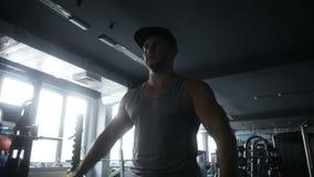 El hombre consigue grande haciendo la mosca del hombro de la pesa de gimnasia metrajes