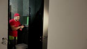 El hombre, el constructor, utiliza un destornillador inalámbrico atornilla las puertas de cristal negras almacen de metraje de vídeo