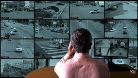El hombre controla el sistema de supervisión almacen de metraje de vídeo
