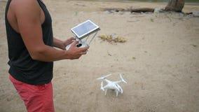 El hombre controla Quadcopter que vuela vía teledirigido con la pantalla del artilugio de la tableta El abejón saca en la playa H almacen de metraje de vídeo