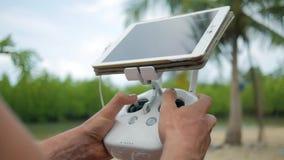 El hombre controla Quadcopter que vuela vía teledirigido con la pantalla del artilugio de la tableta Piloto Practice Flight del a almacen de metraje de vídeo