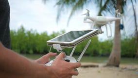 El hombre controla Quadcopter que vuela vía teledirigido con la pantalla del artilugio de la tableta Piloto Practice Flight del a metrajes